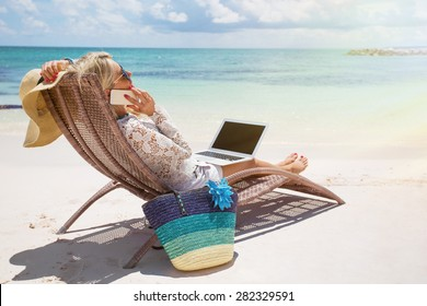 Productive businesswoman working on the beach