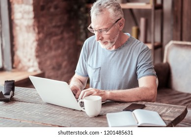 Productive day. Close up of elderly man expressing attention while working with a laptop and sitting at the table