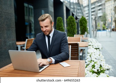 Productive time outside the office. Handsome businessman  in expensive formal suit working with laptop while sitting on summer terrace in outdoor sidewalk cafe