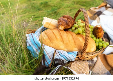 Products in a basket at a picnic: bread, rolls, grapes, apples on a background of green grass.