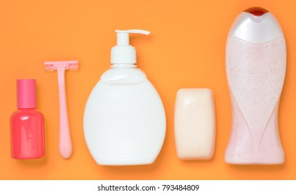 Products for the care of body, hair and personal hygiene on an orange background. A bottle of fragrant perfume, lotion, shampoo, soap, razor. Top view. Trend of minimalism. Flat lay.