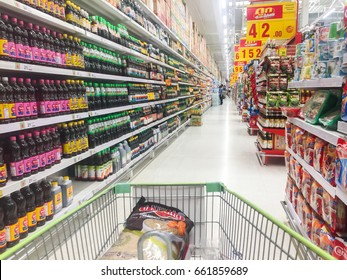 A lot of products in a cart between shelves place by numerous goods in food & drink mode in a local rural supermarket in Thailand, June 14  2017
