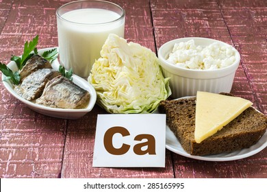 Products containing calcium (sardines in oil, cabbage, milk, cottage cheese, brown bread, cheese) on wooden burgundy background