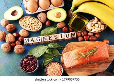Products containing magnesium: bananas, almonds, avocado, nuts and spinach and eggs on table