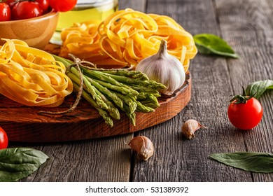 Products for cooking - fresh asparagus, pasta, tomatoes, garlic, olive oil on the old wooden background.