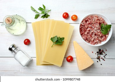 Products for cooking lasagna on wooden background. Top view.