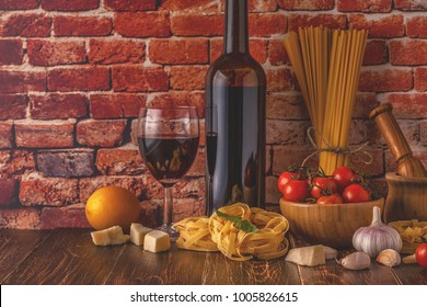 Products for cooking - pasta, tomatoes, garlic, olive oil and red wine. Selective focus.