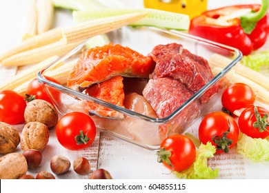 Products for a diet - raw meat of beef and chicken, a salmon and vegetables on a light wooden background. Selective focus.
