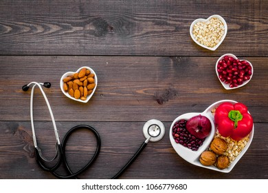 Products good for heart and blood vessels. Vegetables, fruits, nuts in heart shaped bowl near stethoscope on dark wooden background top view copy space