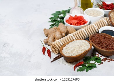products for Japanese cuisine, rice, ginger and spices on white background, top view horizontal