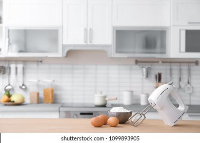 Products, mixer and blurred view of kitchen interior on background