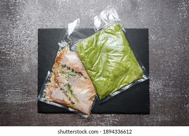 Products in vacuum packaging on black slate board. Chicken meat with herbs and green beans puree, vacuum sealed food ready for sous vide cooking. Sous-vide, new technology cuisine in quarantine time.