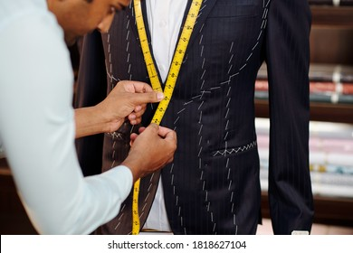 Profesional tailor making bespoke suit for client in his modern stidui