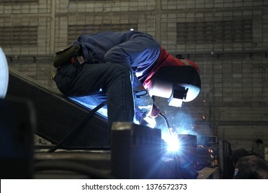 Profesional welder in protective uniform and mask welding metal pipe on the industrial in the industrial workshop.