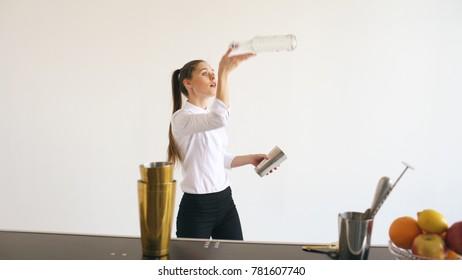 Professinal bartender girl juggling bottles and shaking cocktail at mobile bar table on white background