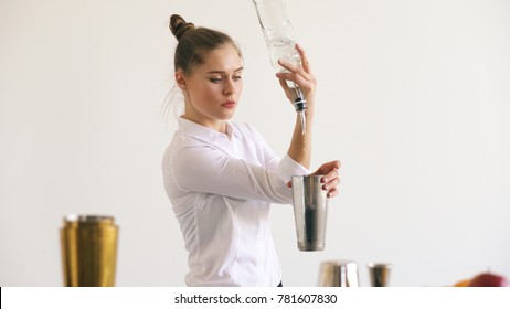 Professinal bartender girl juggling bottles and shaking cocktail at mobile bar table on white background