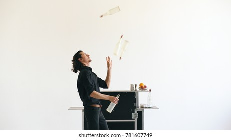 Professinal bartender man juggling bottles and shaking cocktail at mobile bar table on white background