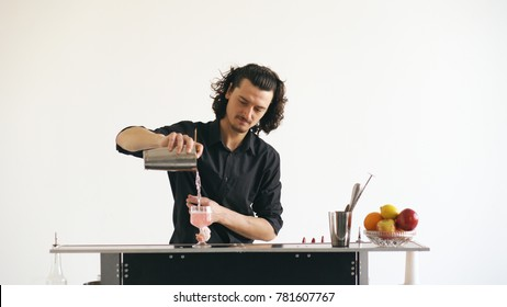 Professinal bartender man shaking cocktail at mobile bar table on white background