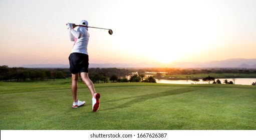 Professinal golf player on golf course. Pro golfer taking a shot at the sunset