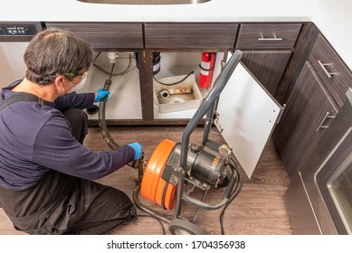 A professinal plumber unclogging a kitchen sink drain using a commercial snake auger, wearing a safety mask per covid guidelines from the US government