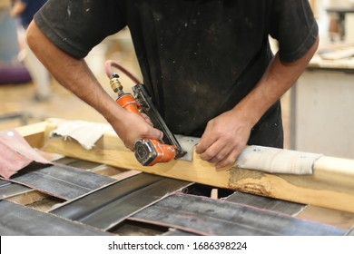 Profession, carpentry and woodwork concept.Upholstery workshop. Upholstery stapler working process. Restoring old chair upholstery. man hands working. man working with pneumatic stapler.