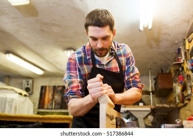 profession, carpentry, woodwork and people concept - carpenter working with plane and wood plank at workshop