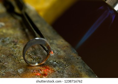 Profession jeweler. Craft jewelery making in the jeweler's workshop. Soldering process. Closeup.