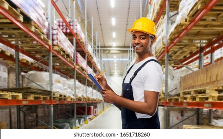 profession, logistic business and people concept - happy smiling indian worker or builder in helmet with clipboard and pencil over warehouse background