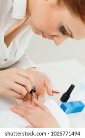 Profession and work. Beauty and health concept. Young professional woman beautician making nails to her female client. Manicurist focus on perfect result.