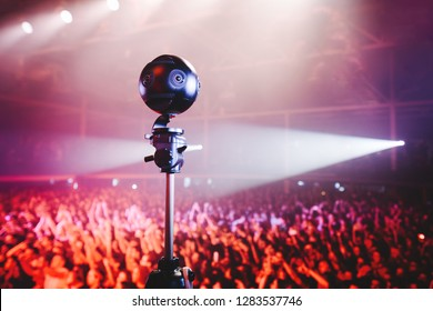Professional 360 camera at music concert on a tripod recording performance on video. silhouettes of crowd in front of bright stage lights.