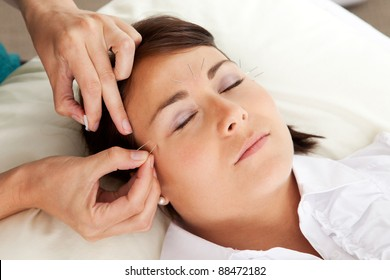 Professional acupuncturist placing a needle near the eye of a patient