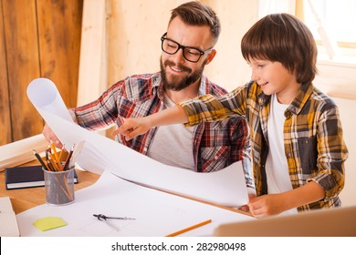 Professional advises from child vision. Cheerful young man holding blueprint while his son pointing at it