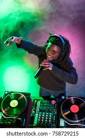 professional african american club DJ in headphones with microphone in nightclub
