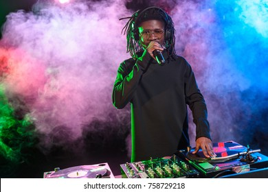 professional african american club DJ with sound mixer and microphone on concert