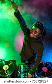 professional african american club DJ in headphones with sound mixer on concert