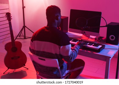 Professional african american musician recording synthesizer in digital studio at home, Music production technology concept.