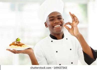 professional African chef holding spaghetti dish and making delicious hand sign