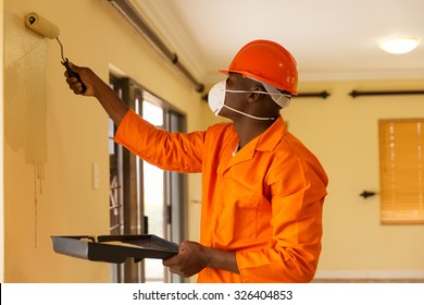 professional african construction worker painting the wall