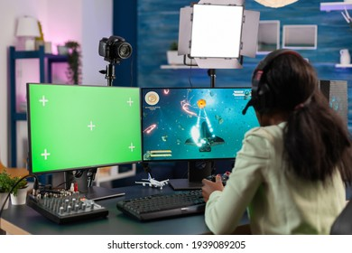 Professional african e sports player streams championship using computer with chroma key. Gamer using pc with greenscreen isolated desktop streaming space shooter video games.
