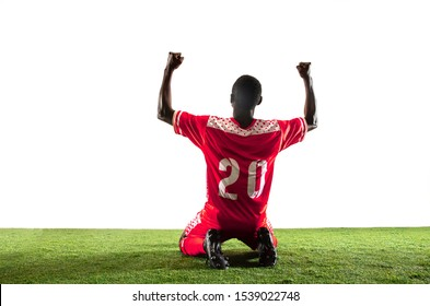Professional african-american football or soccer player of red team in motion isolated on white studio background. Fit man in action, excitement, emotional moment. Concept of movement at gameplay.