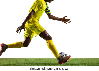 Professional african-american football or soccer player of yellow team in motion isolated on white studio background. Fit man in action, excitement, emotional moment. Concept of movement at gameplay.