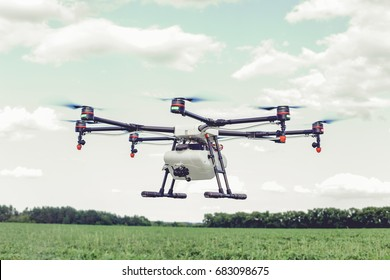 Professional agriculture drone flying and green wheat field, Hovering drone flies in blue sky and taking pictures of green hills.