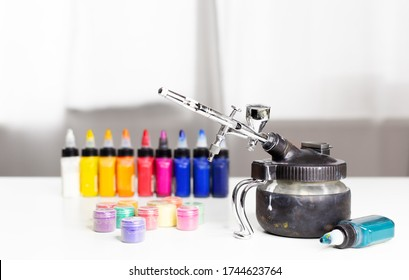 Professional airbrush on a stand with colorful paints in backgroung. Home art equipment. Airbrush work