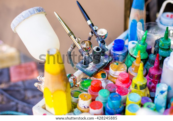 Professional airbrush on a stand with colorful paints in backgroung. Airbrush work