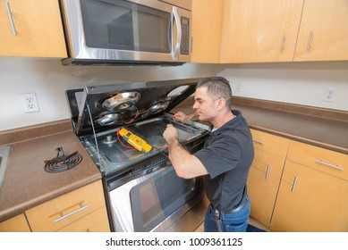 Professional appliance technician testing his voltage meter - working on an electric stovetop, in the kitchen of an apartment.