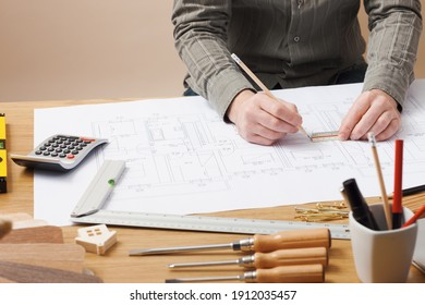 Professional architect and construction engineer working at office desk hands close-up, he is drawing on a building project with a pencil and a ruler