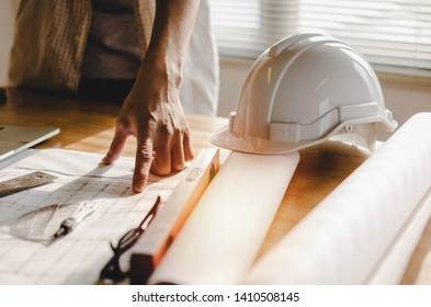 professional architect, engineer or interior planning construction with blueprint on workplace desk in office center at construction site, contractor, construction, engineering and business concept