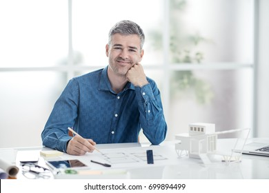 Professional architect sitting at office desk and working, he is checking a project blueprint, engineering and architecture concept