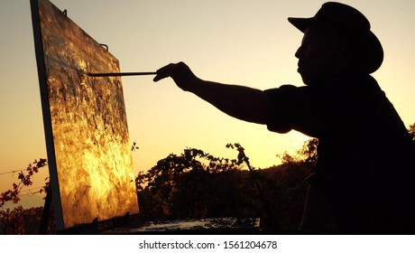 Professional artist paints a picture in nature. Silhouette of an adult man, sunset, abstract autumn landscape. Painting in the open air using a portable easel and a paintbox