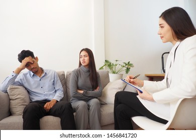 Professional Asian female psychiatrist giving advice to couple having serious relationship problem and difficulties in living together after marriage. Medical mental treatment provided by doctor